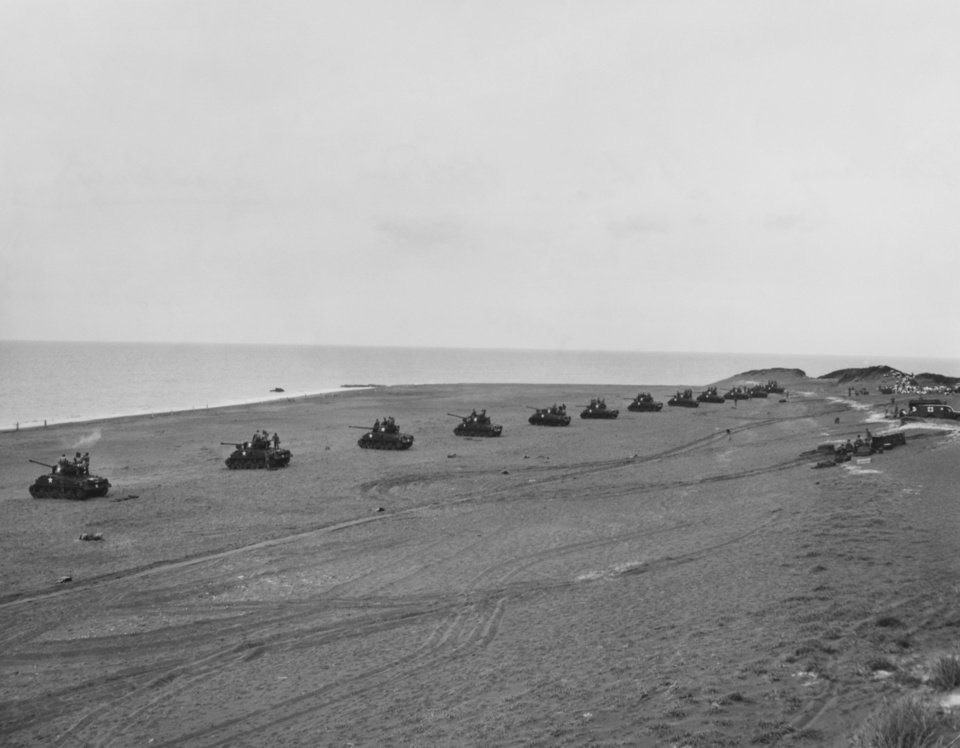 Photo - A long row of General Sherman tanks lined up on a sandy beach on Hokkaido's Pacific coast.  Prepares to fire at an ocean-going target being pulled by a Japanese fishing boat.  Thunderbirds firing the tanks are from Tank Co., 179th Infantry, a unit of the 45th Infantry division. Sherman tanks on Hokkaido's Pacific coast prepare to fire at an ocean-going target in September 1951.  Thunderbirds firing the tanks are from Tank Co., 179th Infantry, a unit of the 45th infantry division.  Photo by Jack Gunter of 45th Division News Photo.  Original undated.  Published in The Daily Oklahoman 11/15/1987.