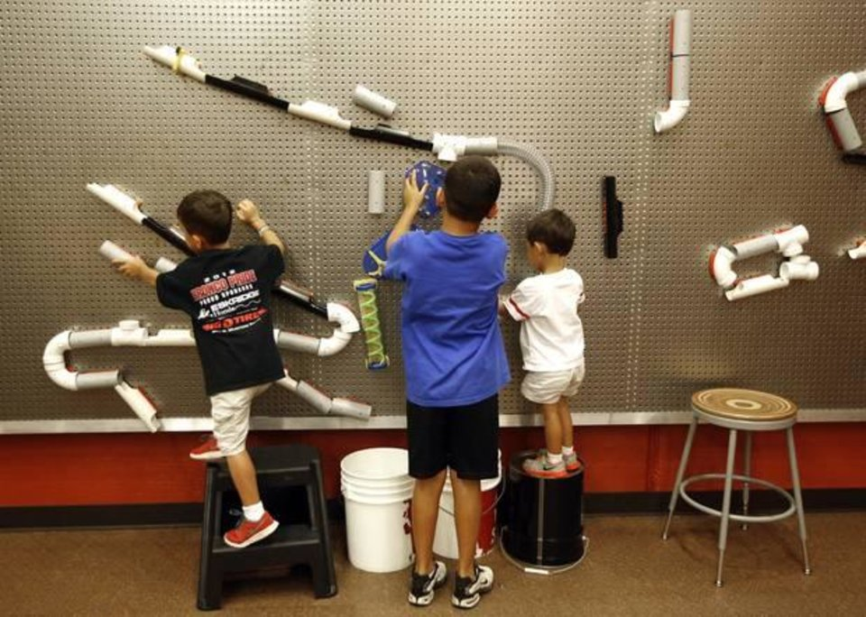 Photo -  Dane,7, left, Davis, 9 and Drew Villanueva,3 work on a project at Science Museum Oklahoma in Oklahoma City, Thursday July 31 , 2014. The brothers were playing in the new Tinkering Garage. Photo By Steve Gooch, The Oklahoman