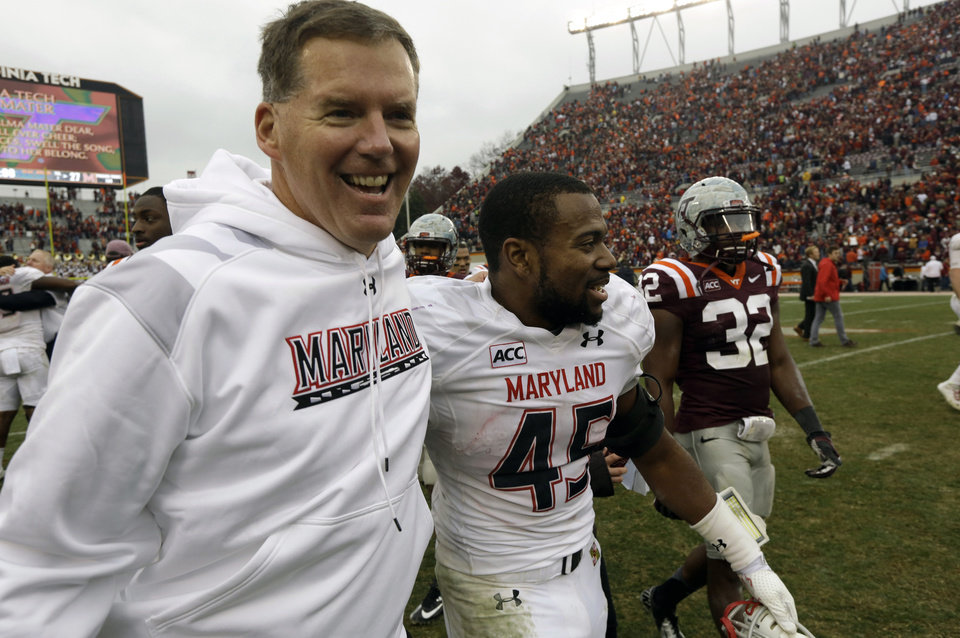 Photo - FILE - In this Nov. 16, 2013, file photo, Maryland head coach Randy Edsall, left, celebrates with Maryland running back Brandon Ross (45) after their team's 27-24 overtime win over Virginia Tech in an NCAA college football game in Blacksburg, Va. Coming off its best season under coach Edsall, Maryland can't wait to mix it up on the football field with Big Ten powerhouses Ohio State, Michigan and Michigan State (AP Photo/Steve Helber, File)