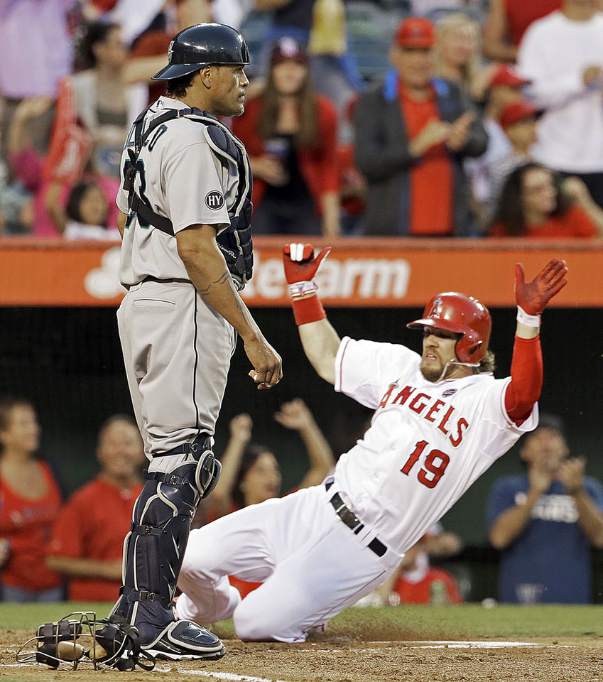 Seattle Mariners catcher Henry Blanco, left, waits for a throw that does not come as Los Angeles Angels Collin Cowgill is one of three runs to score on a hit by Angels' Grant Green in the second inning of a baseball game in Anaheim, Calif., Saturday, Sept. 21, 2013. (AP Photo/Reed Saxon)