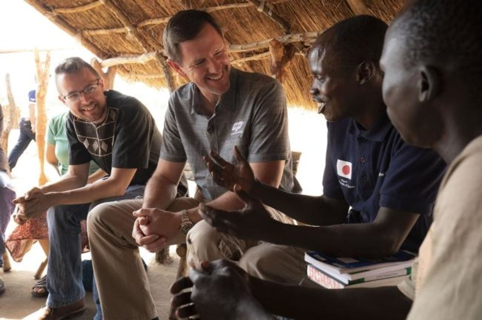 Photo -  Paul Chitwood, International Mission Board president, center, sits with missionary Kevin Singerman, left, and Geofrey Ochan in Uganda. [Chris Carter/IMB]