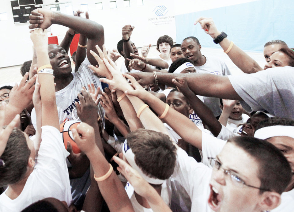 Photo - Basketball player Reggie Jackson, upper left, leads a cheer for the Thunder with children during a 2011 Thunder Youth Basketball Camp at the Boys and Girls Club of Oklahoma County. PHOTO BY NATE BILLINGS, THE OKLAHOMAN