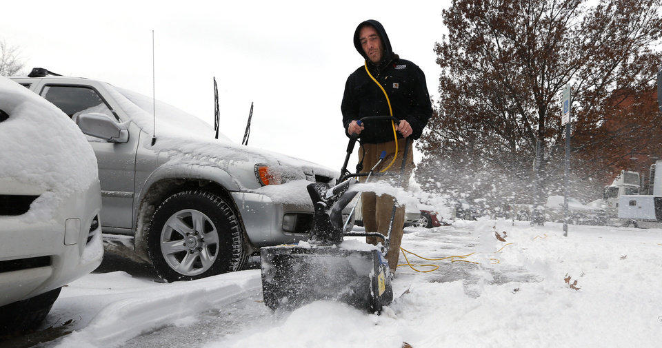 University of Oklahoma (OU) facilities employee Aaron Hanna clears sidewalks near dormitories on Friday, Dec. 6, 2013 in Norman, Okla.  Photo by Steve Sisney, The Oklahoman