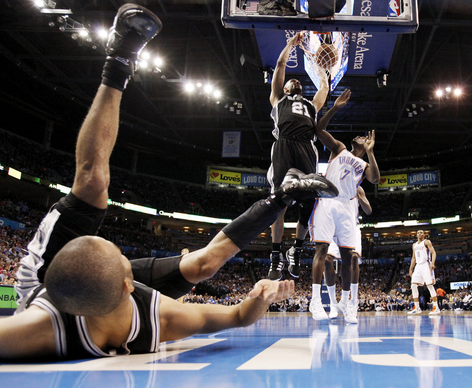 San Antonio's Tony Parker (9) watches from the ground as Tim Duncan (21) dunks a missed shot by Parker next to Oklahoma City's Royal Ivey (7) during the NBA basketball game between the Oklahoma City Thunder and the San Antonio Spurs at Chesapeake Energy Arena in Oklahoma City, Friday, March 16, 2012. Photo by Nate Billings, The Oklahoman