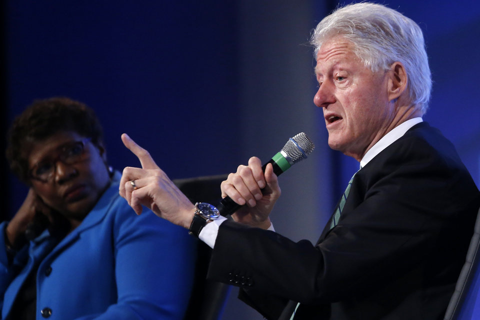 Photo - Former President Bill Clinton answers questions from Gwen Ifill of PBS NewsHour at the 2014 Fiscal Summit organized by the Peter G. Peterson Foundation in Washington, Wednesday, May 14, 2014. Lawmakers and policy experts discussed America's long term debt and economic future. (AP Photo)