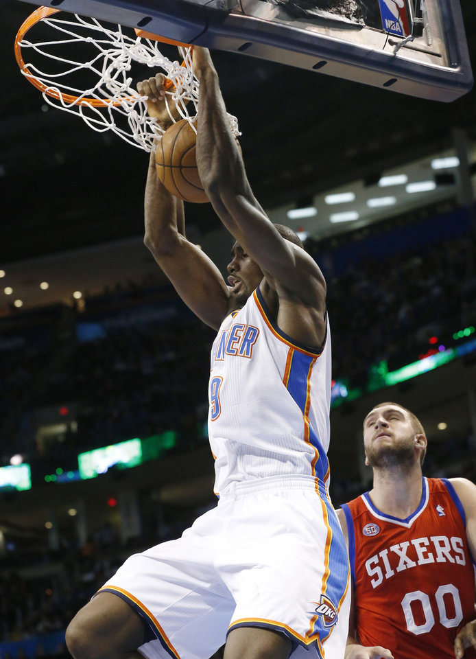 Photo - Oklahoma City Thunder forward Serge Ibaka (9) dunks in front of Philadelphia 76ers forward Spencer Hawes (00) in the fourth quarter of an NBA basketball game in Oklahoma City, Friday, Jan. 4, 2013. Oklahoma City won 109-85. (AP Photo/Sue Ogrocki)