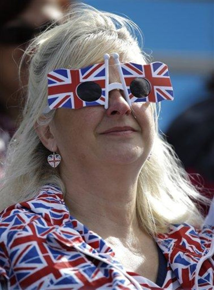 Photo - In this Friday, Aug. 3, 2012 photo, a fan replete with representations of Great Britain's flag watches the competition at the rowing venue in Eton Dorney, near Windsor, England, at the 2012 Summer Olympics in London. Patriotism and the games have always gone together, but gone are the days when one just waved a flag. Now flags are worn, seen all over London and especially at Olympic Park and other spots where the games are being played. (AP Photo/Natacha Pisarenko)
