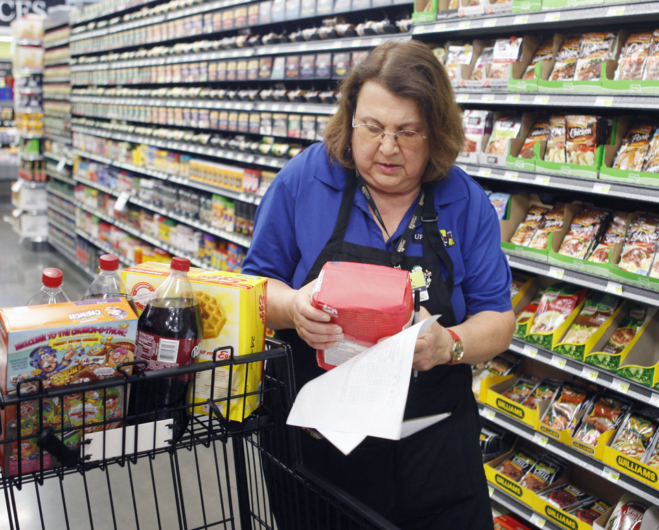 Buy For Less employee Linda Pelletier pulls shopping list items for a customer�s Internet order at Uptown Grocery in Edmond. Photo By Paul Hellstern, The Oklahoman