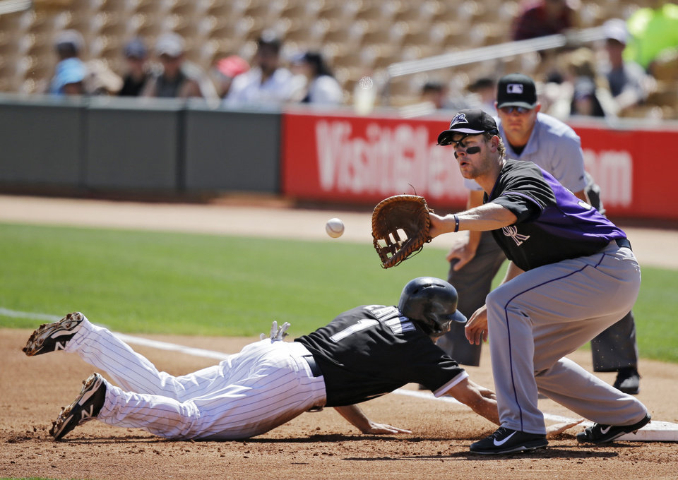 Photo - Chicago White Sox's Adam Eaton (1) dives safely back into first as Colorado Rockies first baseman Justin Morneau waits for the pickoff throw in the first inning of a spring exhibition baseball game Tuesday, March 25, 2014, in Glendale, Ariz. (AP Photo/Mark Duncan)