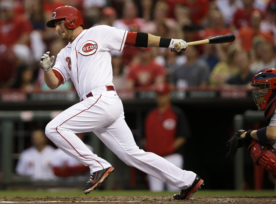 Photo - Cincinnati Reds' Zack Cozart follows through on a hit off St. Louis Cardinals starting pitcher Jaime Garcia to drive in a run in the fifth inning of a baseball game, Saturday, May 24, 2014, in Cincinnati. (AP Photo/Al Behrman)