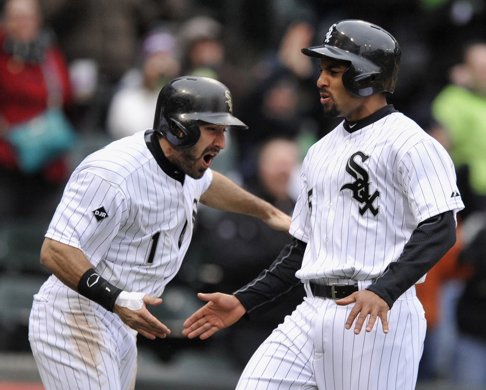 Photo - Chicago White Sox's Adam Eaton (1) celebrates with teammate Marcus Semien, right, after both scored on a Jose Abreu three-RBI triple during the six inning of an baseball game against the Minnesota Twins in Chicago, Thursday, April 3, 2014. (AP Photo/Paul Beaty)