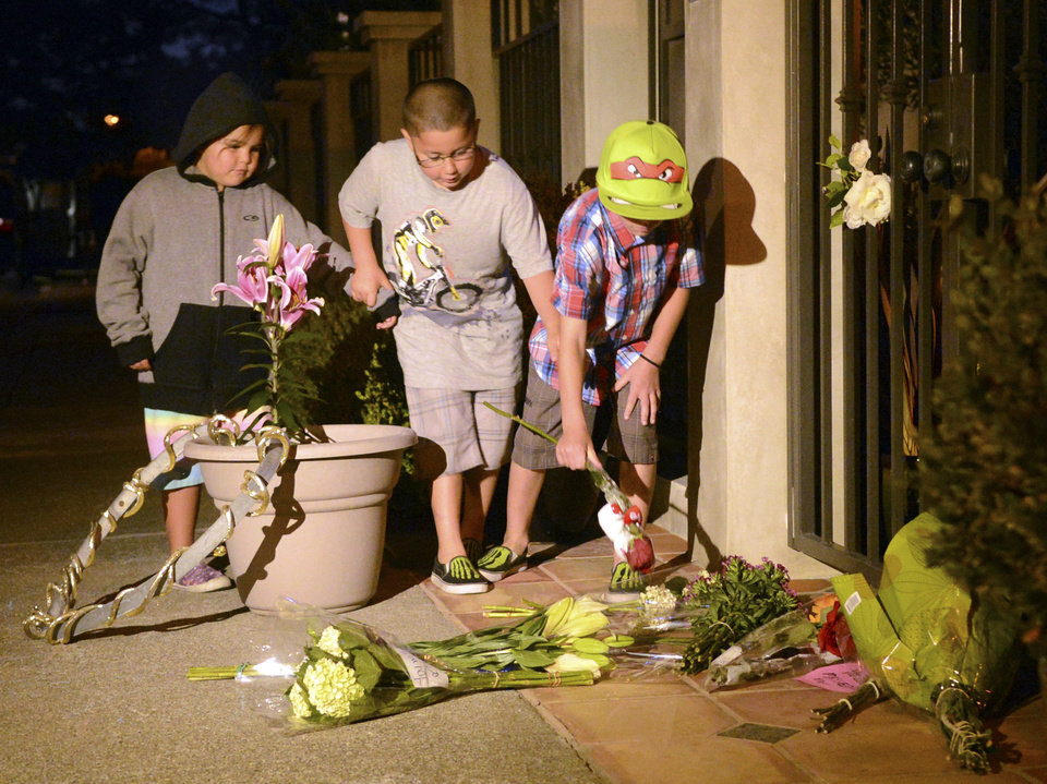 Photo - In this photo taken on Monday, Aug. 11, 2014, from left, Angelina McLaren, 5, Daniel McLaren, 7, and Dylan Bender, 10, of Hayward, place flowers on the sidewalk in front of the home of actor Robin Williams in Tiburon, Calif. Williams died Monday in an apparent suicide at his San Francisco Bay Area home, according to the sheriff's office in Marin County, north of San Francisco. (AP Photo/Marin Independent Journal, Alan Dep)