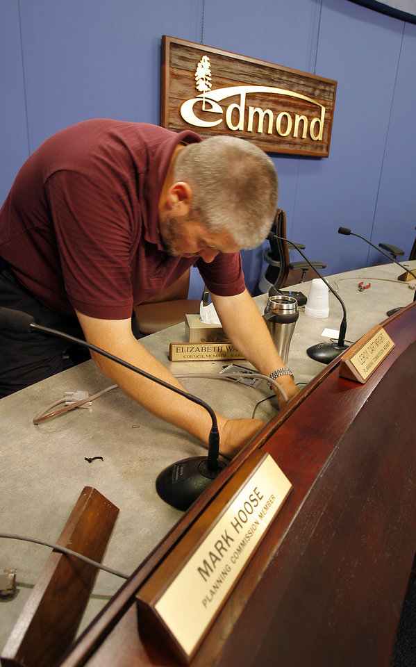 Photo - REPLACE / REPLACEMENT: Kevin Carr, director of IT,  pulls the wiring out for the old voting machines that are being taken out and replaced in the Edmond City Council chambers, Wednesday,  June 17, 2009. Photo By David McDaniel, The Oklahoman. ORG XMIT: KOD