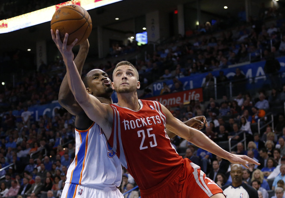 Photo - Houston Rockets forward Chandler Parsons (25) shoots in front of Oklahoma City Thunder forward Serge Ibaka (9) in the second quarter of an NBA basketball game in Oklahoma City, Tuesday, March 11, 2014. (AP Photo/Sue Ogrocki)