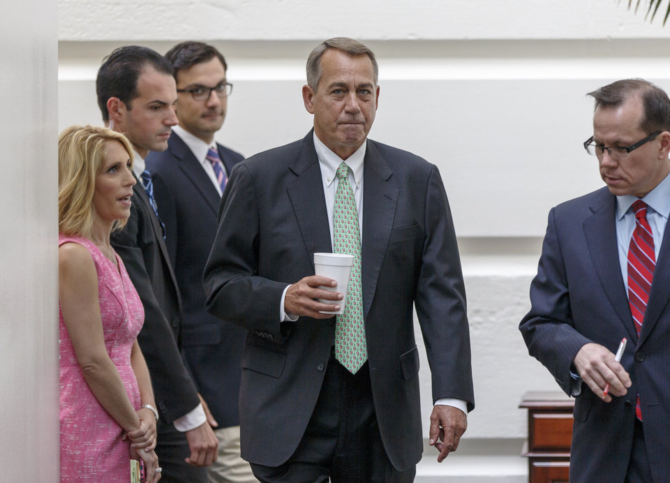 Photo - House Speaker John Boehner of Ohio arrives for a closed-door meeting of House Republicans on Capitol Hill in Washington, Friday, Aug. 1, 2014, to deal with the border crisis, a day after Congress was supposed to go into its August recess. (AP Photo/J. Scott Applewhite)