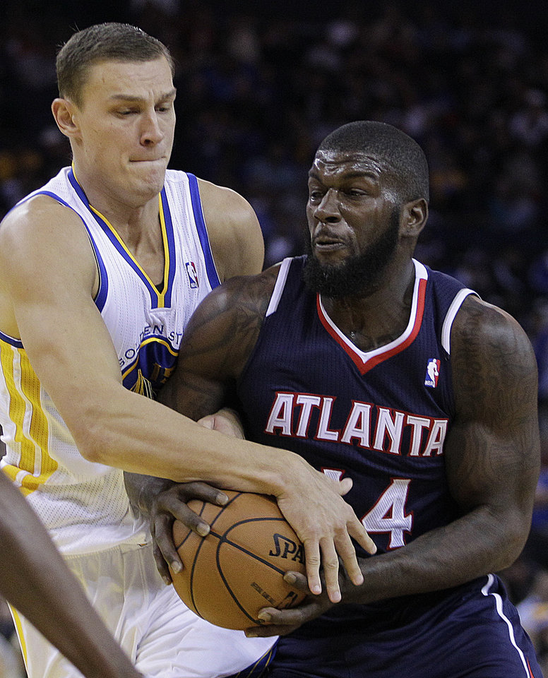 Atlanta Hawks\' Ivan Johnson, right, and Golden State Warriors\' Andris Biedrins fight for the ball during the first half of an NBA basketball game Wednesday, Nov. 14, 2012, in Oakland, Calif. (AP Photo/Ben Margot)