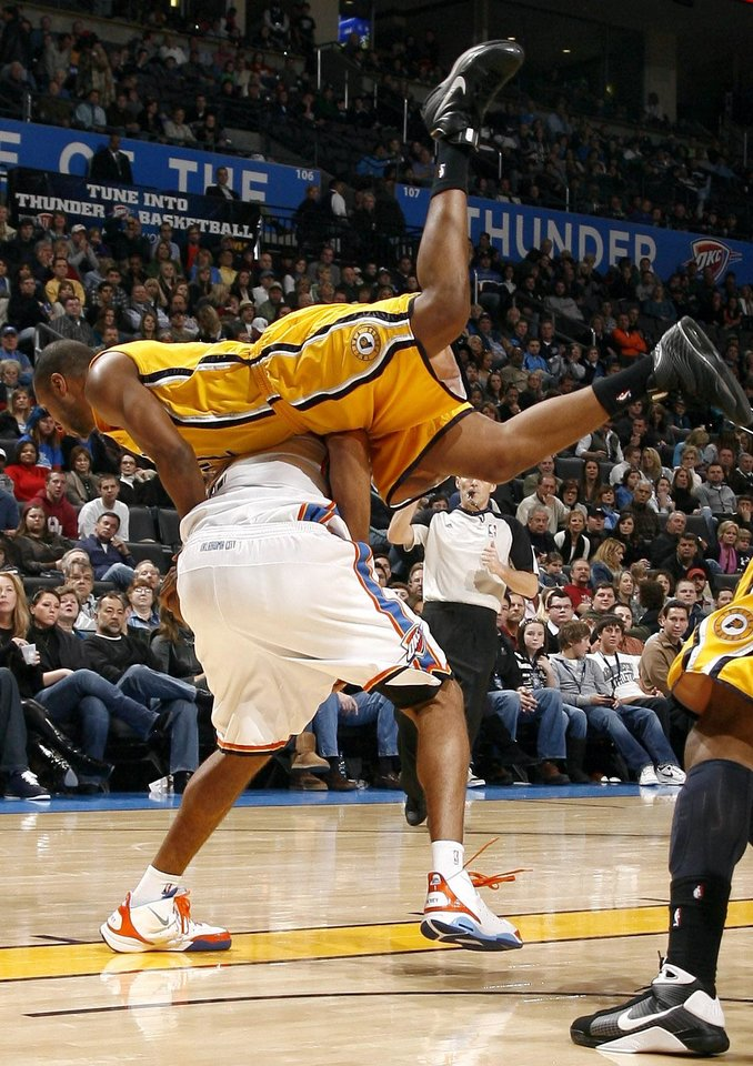 Indiana's A.J. Price tumbles over Oklahoma City's Thabo Sefolosha during the basketball game between the Oklahoma City Thunder and the Indiana Pacers, Saturday, Jan. 9, 2010 at the Ford Center in Oklahoma CIty. Photo by Sarah Phipps, The Oklahoman