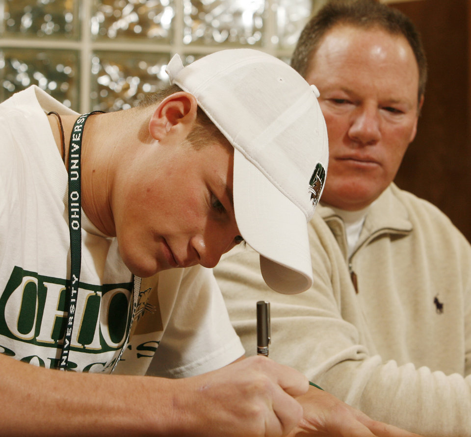 Photo - Tyler Tettleton signs a letter of intent to play college football while his father Mickey Tettleton watches at Norman North High School in  Norman, Okla. on Wednesday, Feb. 4, 2009.    Photo by Steve Sisney, The Oklahoman