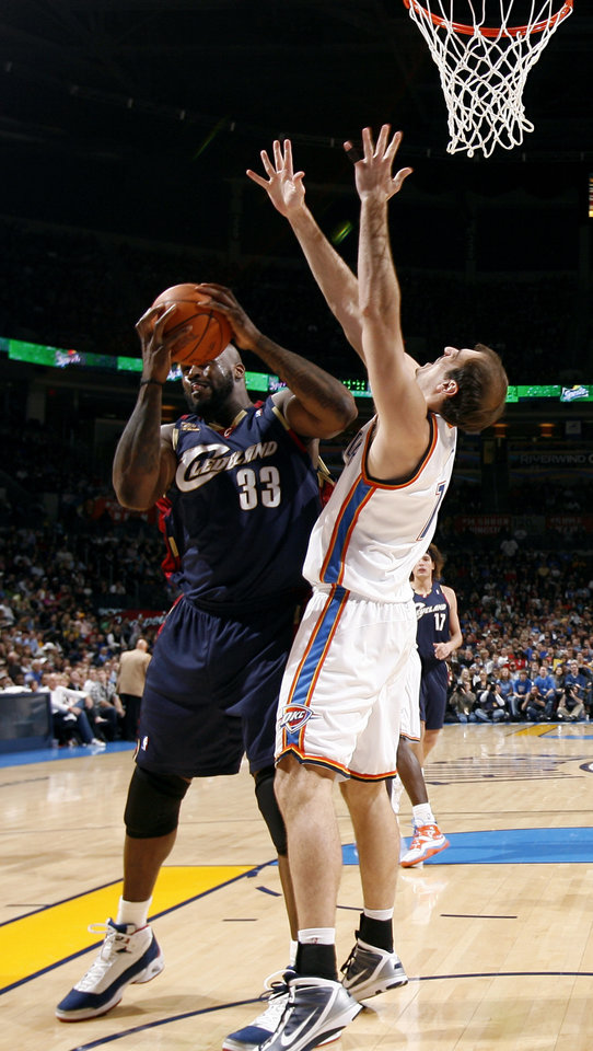 Photo - Oklahoma City's Nenad Krstic (12) defends against Cleveland's Shaquille O'Neal (33) during the NBA game between the Oklahoma City Thunder and the Cleveland Cavaliers, Sunday, Dec. 13, 2009, at the Ford Center in Oklahoma City. Photo by Sarah Phipps, The Oklahoman