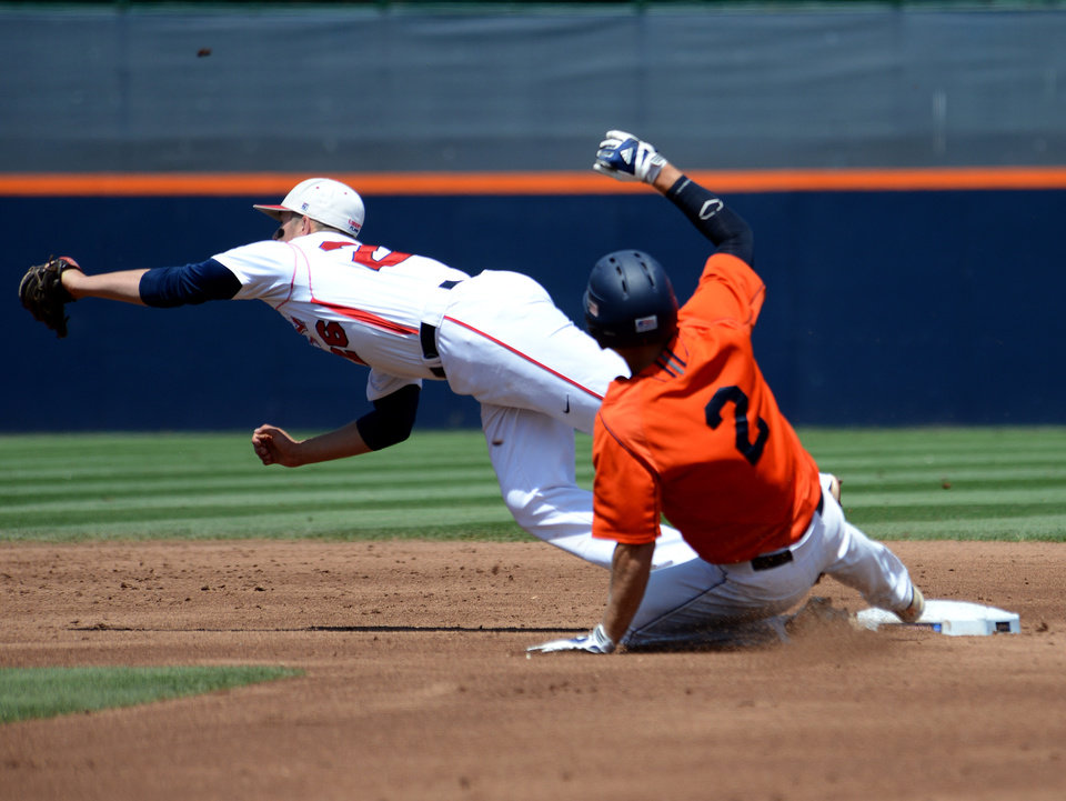 Photo - Liberty's Dalton Britt, left, reaches for a ball but can't make the tag on Bucknell's Brett Smith during the first inning of an NCAA college baseball regional tournament game in Charlottesville, Va., Saturday, May 31, 2014. (AP Photo/Pat Jarrett)