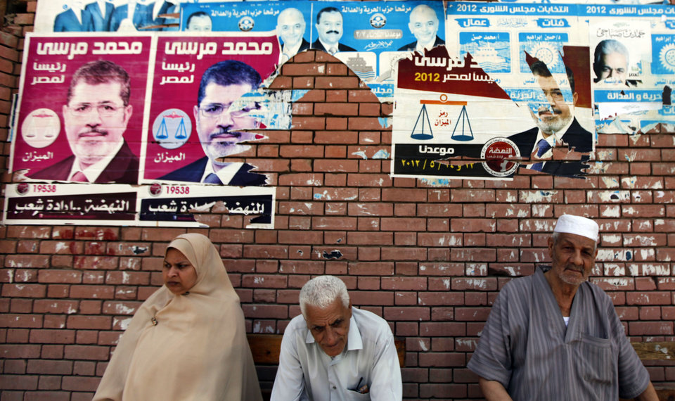 Photo -   Egyptians sit beneath campaign posters supporting the Muslim Brotherhood's presidential candidate Mohammed Morsi outside a polling center as they wait to cast their votes in Alexandria, Egypt, Wednesday, May 23, 2012. More than 15 months after autocratic leader Hosni Mubarak's ouster, Egyptians streamed to polling stations Wednesday to freely choose a president for the first time in generations. Waiting hours in line, some debated to the last minute over their vote in a historic election pitting old regime figures against ascending Islamists.(AP Photo/Khalil Hamra)