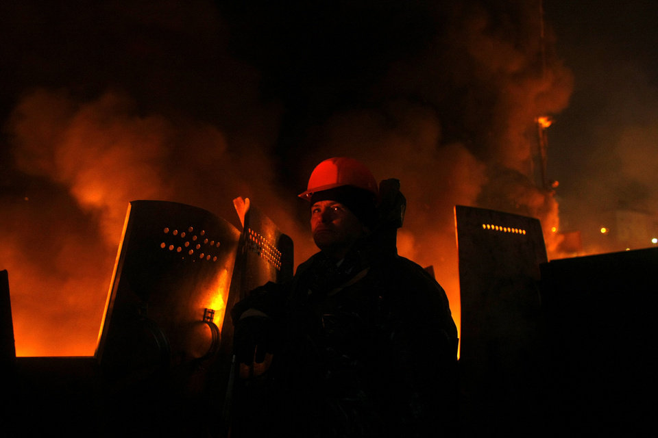 Photo - An anti-government protester mans a barricade at Independence Square in Kiev, Ukraine, Thursday, Feb. 20, 2014. Ukraine's protest leaders and the president they aim to oust called a truce Wednesday, just hours after the military raised fears of a widespread crackdown with a vow to defeat