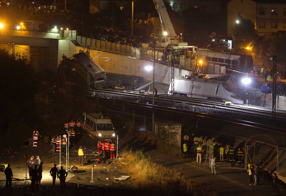 Photo - Emergency personnel conduct rescue operation at the site of derailed trains in Santiago de Compostela, Spain, on Thursday, July 25, 2013. A passenger train derailed Wednesday night on a curvy stretch of track in northwestern Spain, killing at least 40 people caught inside toppled cars and injuring at least 140 in the country's worst rail accident in decades, officials said. (AP Photo/ Lalo Villar)