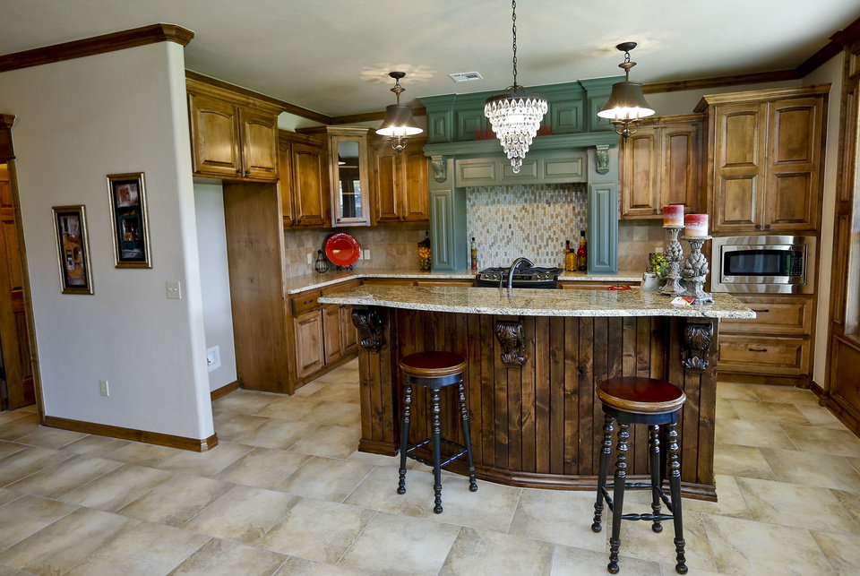 Photo - The kitchen of the House of Hope features a custom island ? granite topped, like the rest of the counters ? for a dining spot, prep area or conversation hub. Maple cabinetry provides ample storage.   CHRIS LANDSBERGER - The Oklahoman
