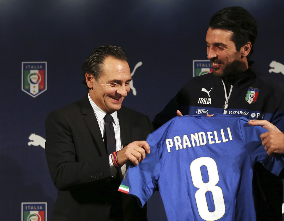 Photo - Italy coach Cesare Prandelli , left, and goalkeeper Gianluigi Buffon show a new Italy soccer team jersey bearing the name of Prandelli  during a press conference in Milan, Italy, Monday, March 3, 2014.  Mario Balotelli is out injured and Daniele De Rossi has been dropped due to a code of ethics violation for Italy's friendly at World Cup holder Spain on Wednesday. Missing two key starters, coach Cesare Prandelli gave Torino forward Ciro Immobile and Parma defender Gabriel Paletta their first call ups to Italy's squad on Sunday. (AP Photo/Antonio Calanni)
