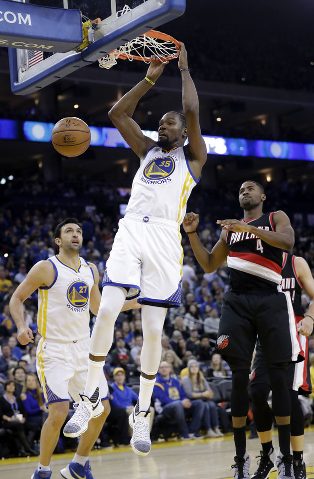 Photo - Golden State Warriors' Kevin Durant (35) dunks against the Portland Trail Blazers during the second half of an NBA basketball game Wednesday, Jan. 4, 2017, in Oakland, Calif. (AP Photo/Marcio Jose Sanchez)
