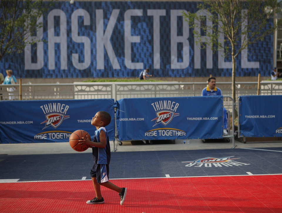 Photo - Anthony Lane II, 4, of Oklahoma CIty shoots a basket before game 4 of the Western Conference Finals in the NBA basketball playoffs between the Dallas Mavericks and the Oklahoma City Thunder at the Oklahoma City Arena in downtown Oklahoma City, Monday, May 23, 2011. Photo by Bryan Terry, The Oklahoman