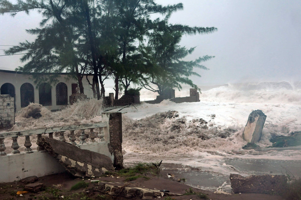 Photo -   Waves, brought by Hurricane Sandy, crash on a house in the Caribbean Terrace neighborhood in eastern Kingston, Jamaica, Wednesday, Oct. 24, 2012. Hurricane Sandy pounded Jamaica with heavy rain as it headed for landfall near the country's most populous city on a track that would carry it across the Caribbean island to Cuba, and a possible threat to Florida. (AP Photo/Collin Reid)