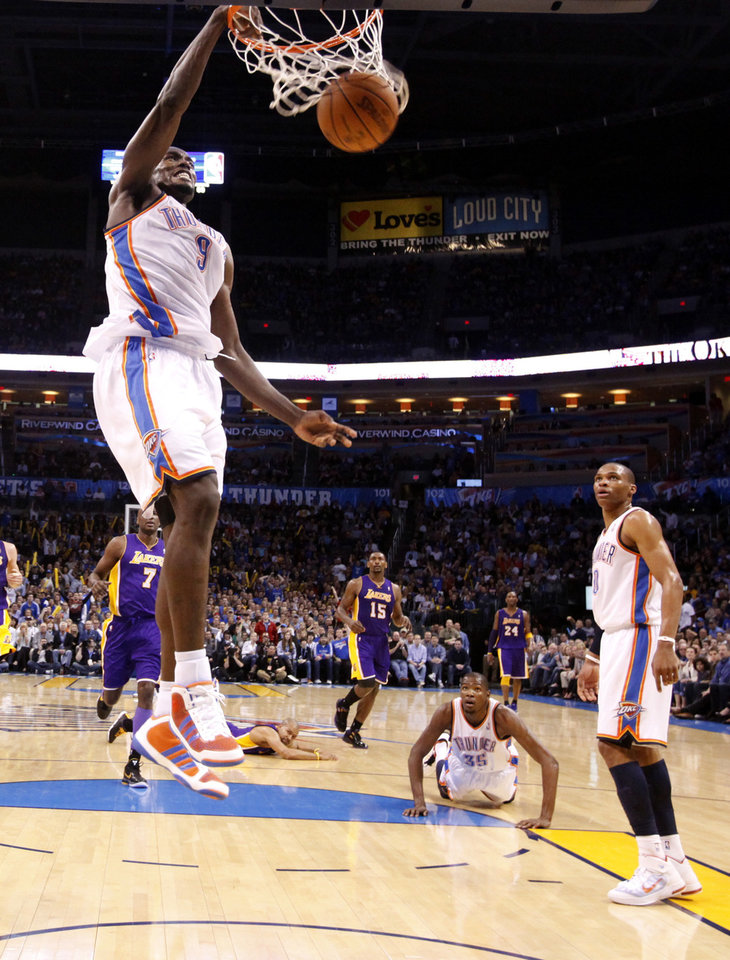 Photo - Oklahoma City's Serge Ibaka (9) dunks as Kevin Durant (35) and Russell Westbrook (0) look on during the NBA basketball game between the Oklahoma City Thunder and the Los Angeles Lakers, Sunday, Feb. 27, 2011, at the Oklahoma City Arena.Photo by Sarah Phipps, The Oklahoman