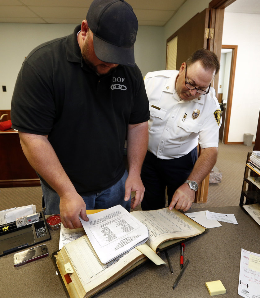 Photo -  IOOF Cemetery manager Tim Bowling, left, and Deputy Fire Chief Jim Bailey look through records for evidence of a mass burial in 1918 of the victims of a fire at the state mental hospital. PHOTO BY STEVE SISNEY, THE OKLAHOMAN   STEVE SISNEY -