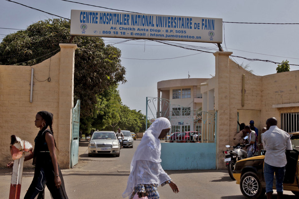 Photo - Women walk past the entrance to the  University Hospital Fann, where a man is being treated for symptoms of the Ebola virus in Dakar, Senegal,  Friday, Aug. 29, 2014. A man infected with Ebola traveled to Senegal, becoming the first recorded in this country of an outbreak that has hit four other West African countries and has killed more than 1,5000 people, the Ministry of Health said Friday.(AP Photo/Jane Hahn)