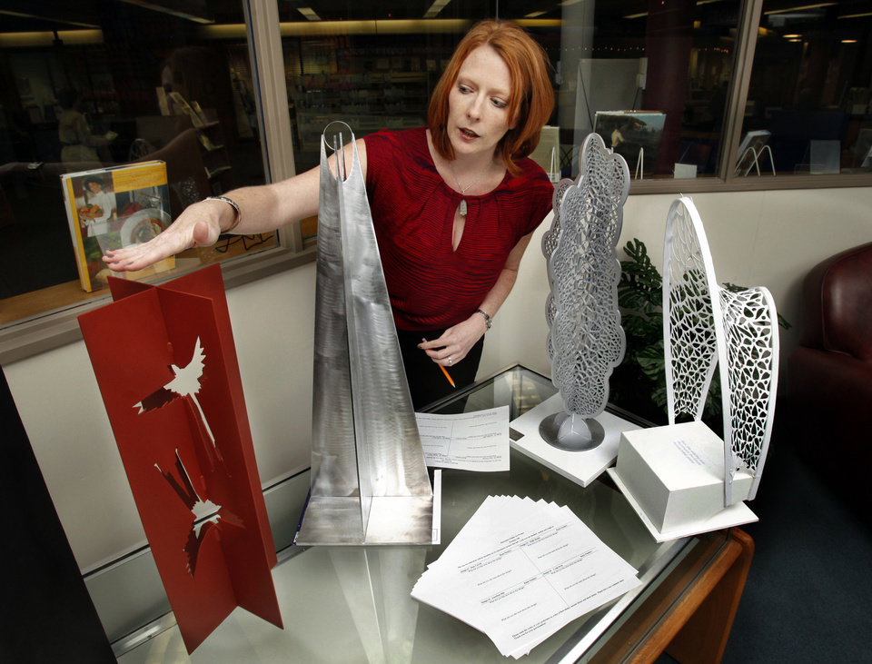 Erinn Gavaghan, director of the Norman Arts Council, shows artists� proposed sculptures for downtown Norman. She points to Sun Dial by Craig Swan, one of two chosen for installation. The other selection is Silver Lining by Jonathan Hils, which is the third piece from the left. PHOTO BY STEVE SISNEY, THE OKLAHOMAN