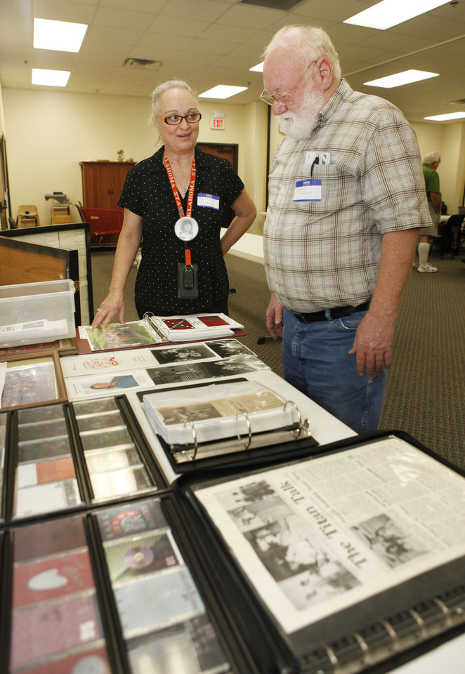 Gwen Bell Glenn, class of 1969, and John Blood, class of '67, look at memorabilia as Carl Albert High School classes of the 1960s held a get-together Saturday at Soldier Creek Baptist Church in Midwest City. Photo by PAUL HELLSTERN, The Oklahoman