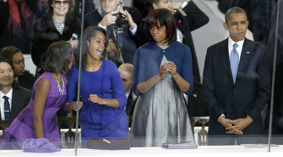 President Barack Obama, right, and first lady Michelle Obama watch the Inaugural parade down Pennsylvania Avenue as their daughters, Sasha, left, and Malia, second from left, dance in the presidential box near the White House, Monday, Jan. 21, 2013, in Washington. Thousands marched during the 57th Presidential Inauguration parade after the ceremonial swearing-in of President Barack Obama. (AP Photo/Gerald Herbert) ORG XMIT: DCMS137