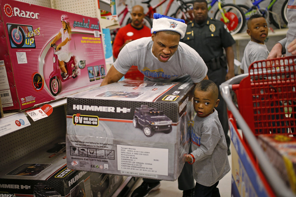 Photo - Russell Westbrook, of the Oklahoma City Thunder, jokes around with Jeremiah Rogers, 3, as he helps load a toy in his cart during on Wednesday, December 18, 2013. The entire NBA team took 10 families   directly affected by the Moore tornado on a shopping spree during the sixth annual event that is part of the Thunder Holiday Assist initiative. PHOTO BY BRYAN TERRY, The Oklahoman