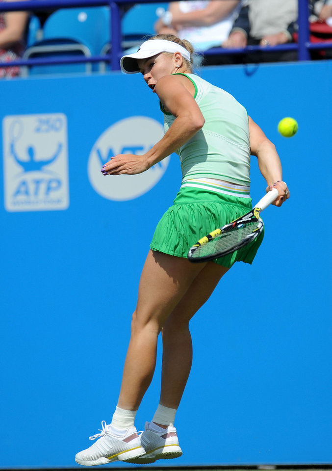 Photo - Denmark's Caroline Wozniacki plays a point from behind her back to Germany's Angelique Kerber during their semifinal match at the Aegon International tennis tournament at Devonshire Park, Eastbourne, southern England, Friday June 20, 2014. (AP Photo/PA, Clive Gee) UNITED KINGDOM OUT  NO SALES  NO ARCHIVE