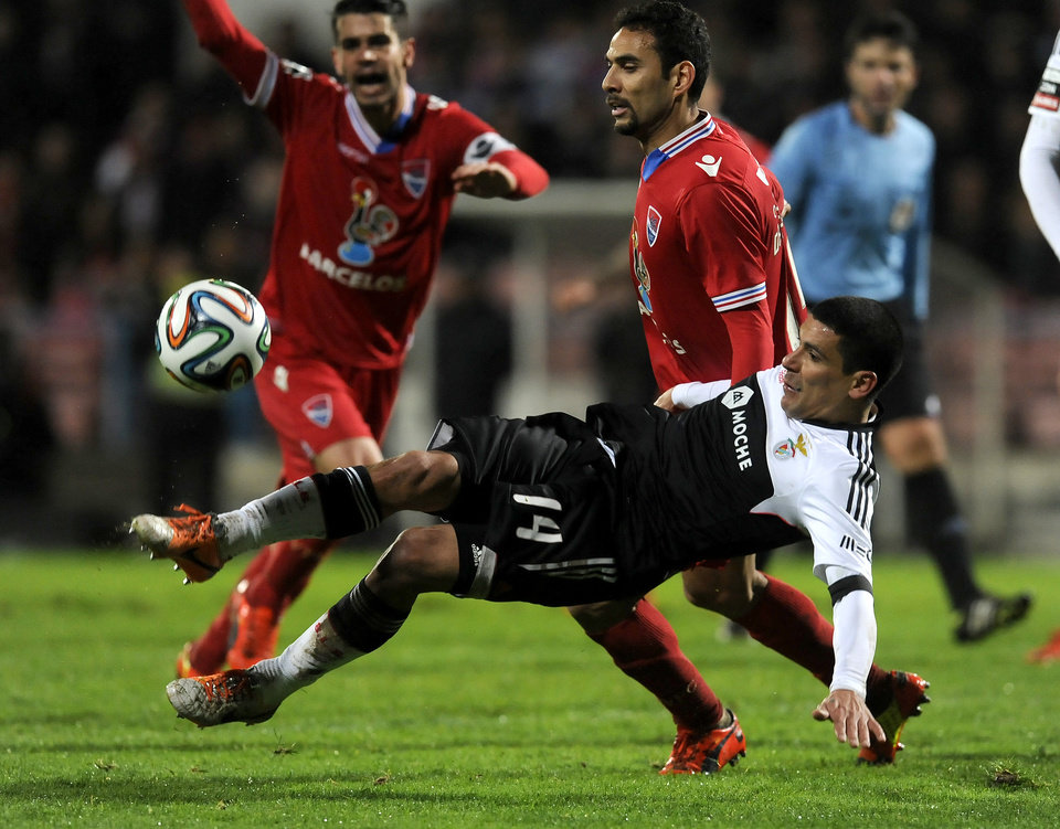 Photo - Benfica's Maxi Pereira, front, from Uruguay attempts a shot past by Gil Vicente's Danielson Trindade, from Brazil, in a Portuguese League soccer match at the Cidade de Barcelos stadium, in Barcelos, northern Portugal, Saturday, Feb. 1, 2014. The match ended in a 1-1 draw. (AP Photo/Paulo Duarte)
