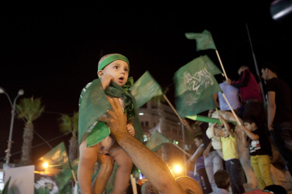 Photo - A Palestinian Hamas supporter holds up a little girl wearing green flags as people gather in the streets during celebrations for the cease-fire between Palestinians and Israelis, in the West bank city of Ramallah, Tuesday, Aug. 26, 2014.  Israel and Hamas agreed Tuesday to an open-ended cease-fire, halting a seven-week war that killed more than 2,200 people, the vast majority Palestinians, left tens of thousands in Gaza homeless and devastated entire neighborhoods in the blockaded territory. (AP Photo/Majdi Mohammed)