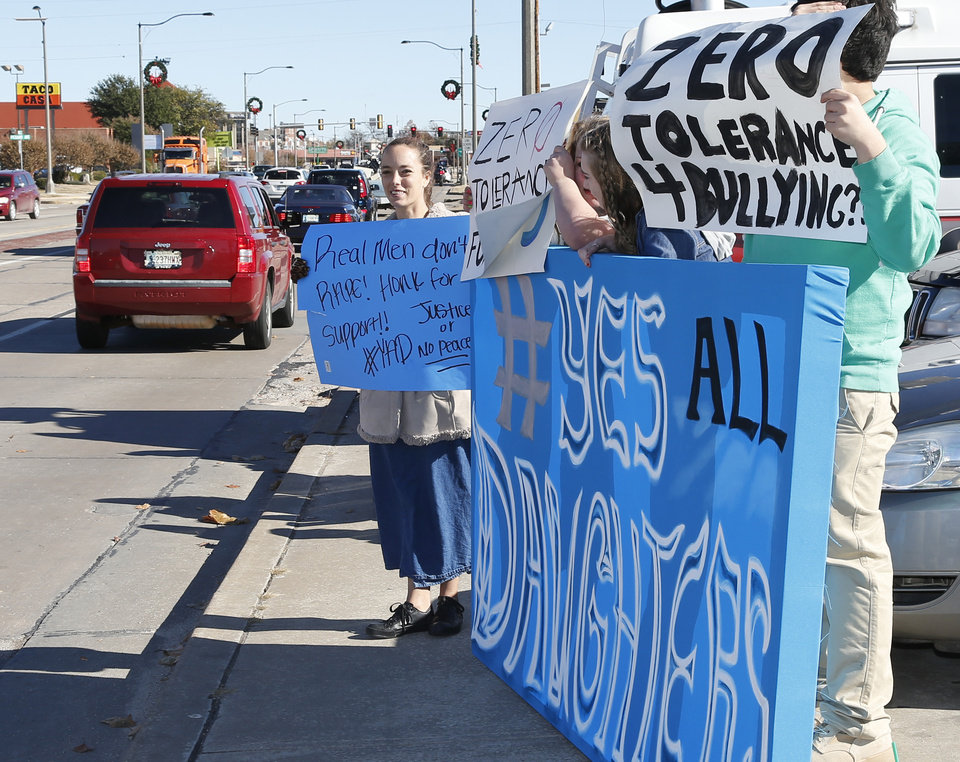 Photo - Students and parents hold signs during a protest across the street from Norman High School in Norman, Okla., Monday, Nov. 24, 2014. Allegations by three girls at  the high school who say they were raped by the same male student have led to a police investigation and protests by students who say school officials have mishandled the case and subsequent bullying. (AP Photo/Sue Ogrocki)