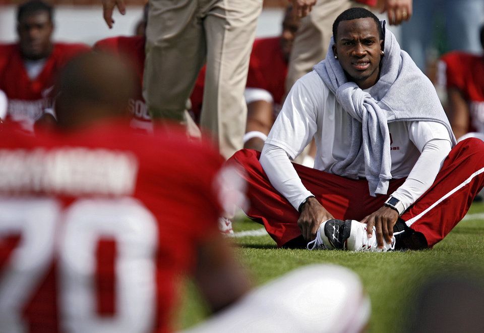 Photo - Oklahoma's Ryan Broyles wears street clothes while he stretches out with the team before the college football game between the University of Oklahoma Sooners (OU) and the Baylor University Bears at Gaylord Family-Oklahoma Memorial Stadium on Saturday, Oct. 10, 2009, in Norman, Okla. 