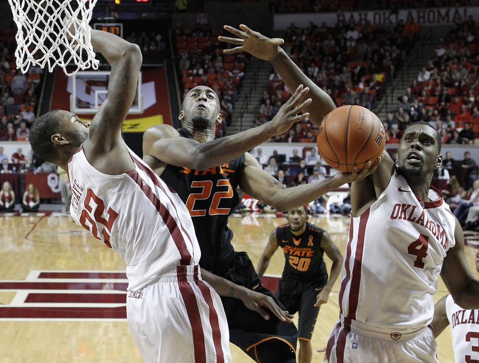 Oklahoma State guard Markel Brown (22) goes up for a shot between Oklahoma forward Amath M'Baye (22) and forward Andrew Fitzgerald (4) in the second half of an NCAA college basketball game in Norman, Okla., Saturday, Jan. 12, 2013. Oklahoma won 77-68. (AP Photo/Sue Ogrocki) ORG XMIT: OKSO103
