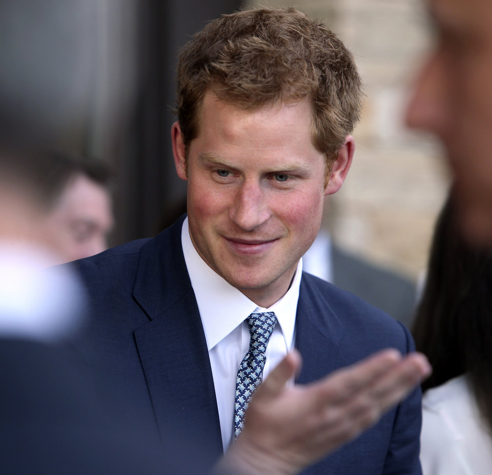 Photo - Britain's Prince Harry talks with a guest at a reception at the Sanctuary Golf Course in Sedalia, Colo., south of Denver on Friday, May 10, 2013. (AP Photo/Ed Andrieski, Pool)