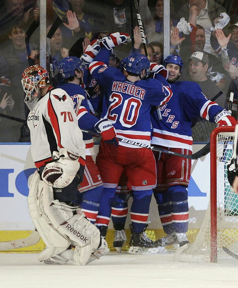 Photo -   Washington Capitals goalie Braden Holtby (70) skates away as New York Rangers' Chris Kreider (20) celebrates with teammates after a goal by Brad Richards during the third period of Game 1 in the second round of the NHL hockey Stanley Cup playoffs Saturday, April 28, 2012, in New York. The Rangers won 3-1. (AP Photo/Frank Franklin II)