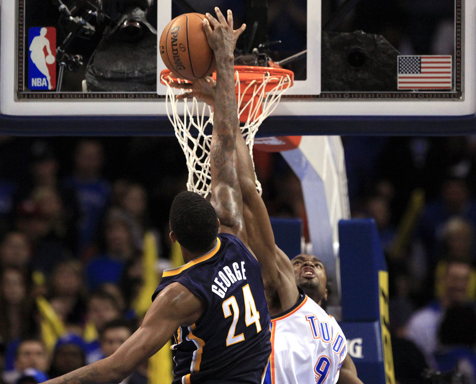 Photo - Oklahoma City's Serge Ibaka (9) blocks the shot of Indiana's Paul George (24) during the NBA game between the Indiana Pacers and the Oklahoma City Thunder at the Chesapeake Energy Arena   Sunday,Dec. 9, 2012. Photo by Sarah Phipps, The Oklahoman