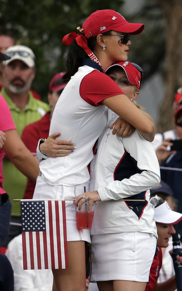 Photo - United States' Michelle Wie, left, hugs teammate Morgan Pressel on the 18th green after Wie lost her singles match against Europe's Caroline Hedwall, from Sweden, to allow Europe to retain the Solheim Cup during the golf tournament ,Sunday, Aug. 18, 2013, in Parker, Colo. (AP Photo/Chris Carlson)