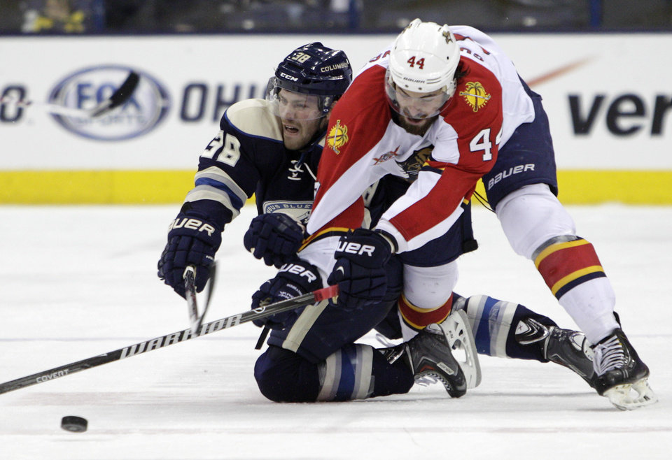 Photo - Florida Panthers' Erik Gudbranson, right, and Columbus Blue Jackets' Boone Jenner chase a loose puck during the second period of an NHL hockey game Saturday, Feb. 1, 2014, in Columbus, Ohio. (AP Photo/Jay LaPrete)